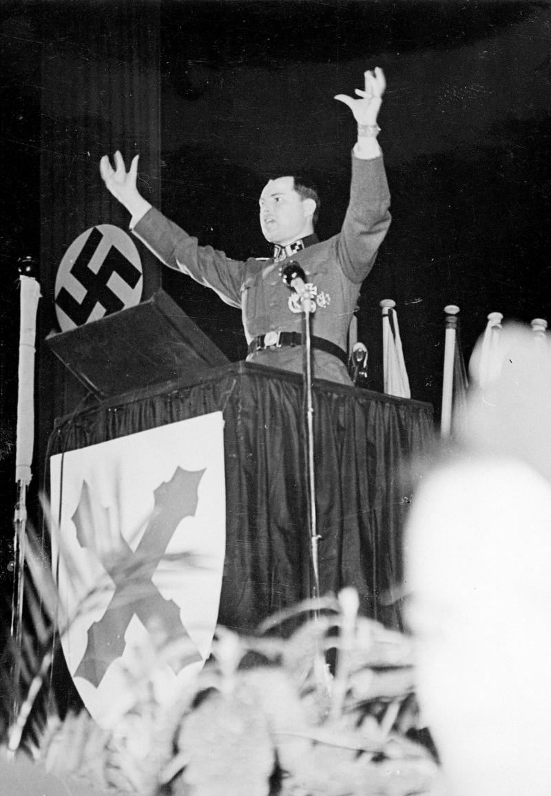 Léon Degrelle en plein discours à la manifestation de la Waffen-SS française donnée en mars 1944 au Palais de Chaillot. Devant son pupitre, la bannière de la Division SS Wallonie évoque le mythique Duché de Bourgogne.